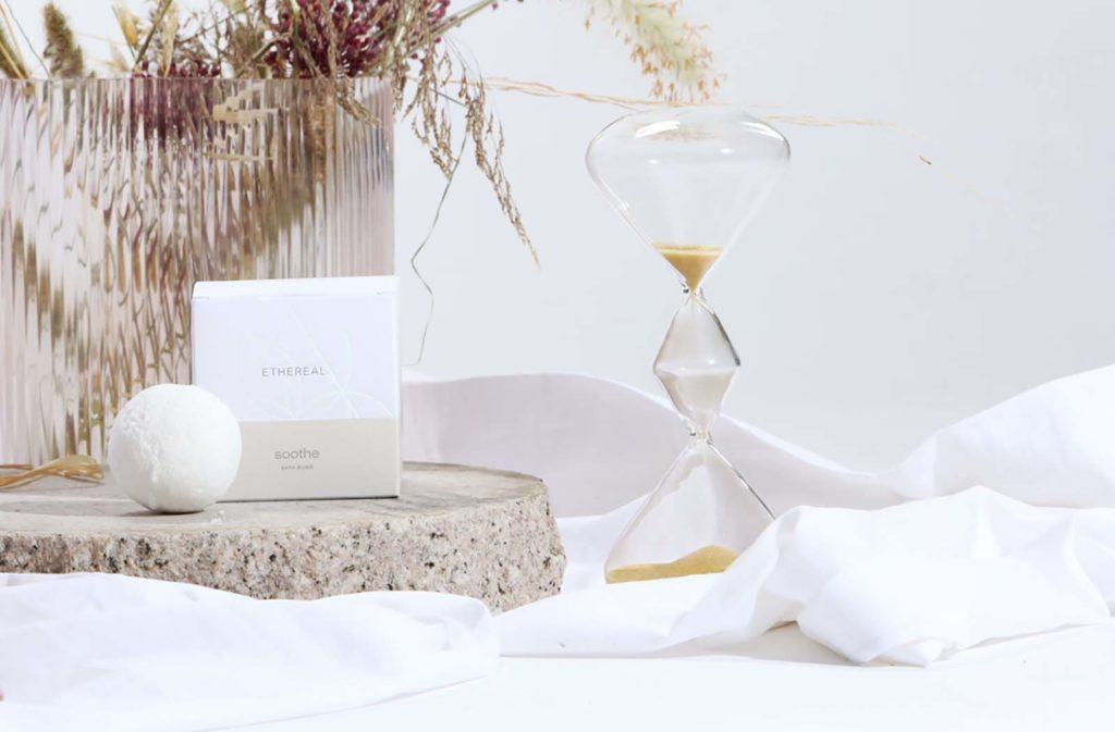 bathbom soothe σε σύνθεση με κλεψύδρα και λευκό φόντο